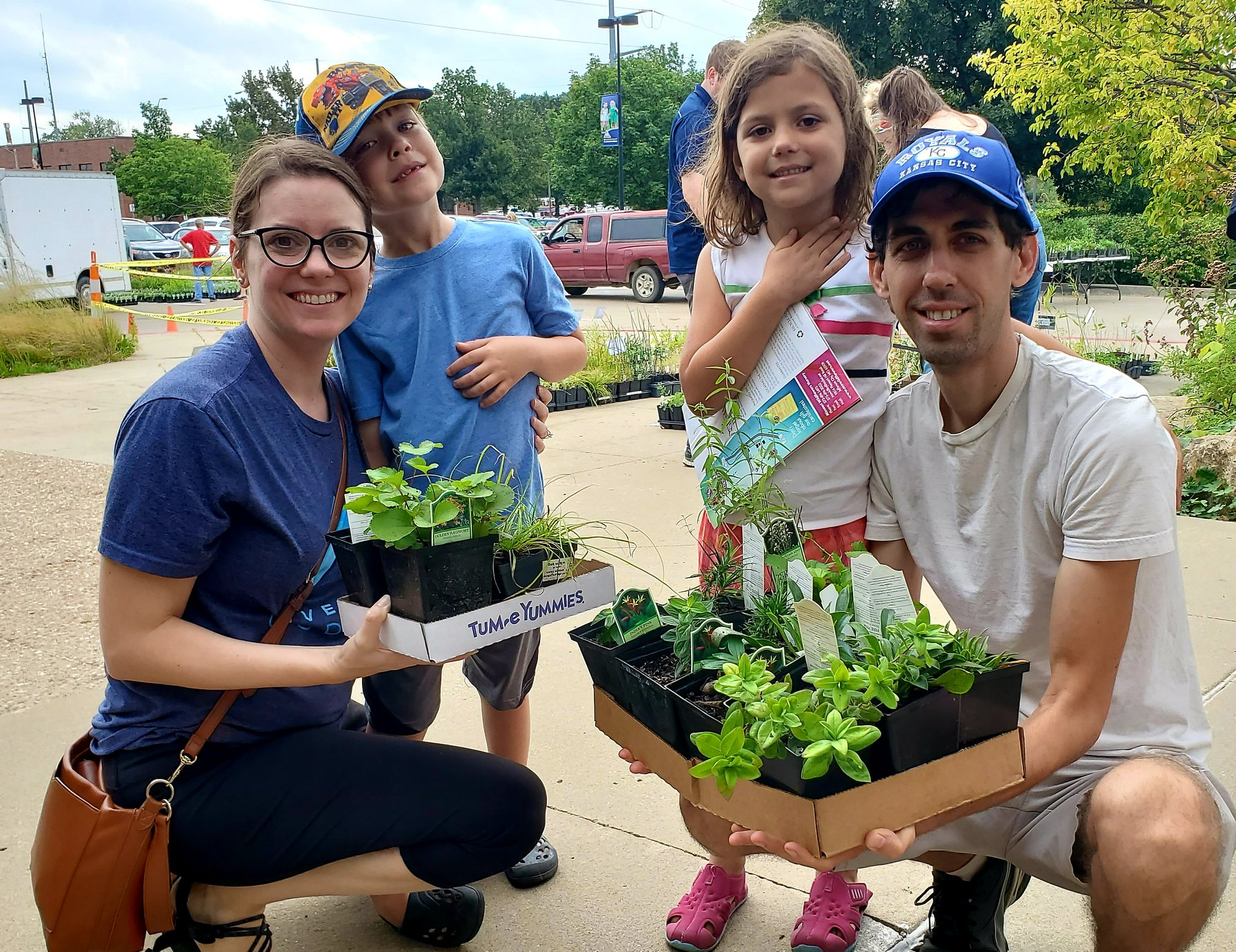 A young family picking out native plants at a MPF plant sale