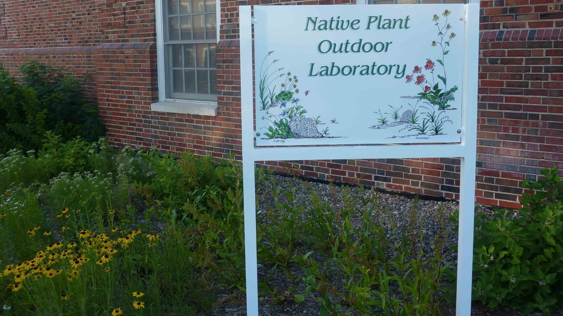 """White sign that reads """"Native Plant Outdoor Laboratory"""""""
